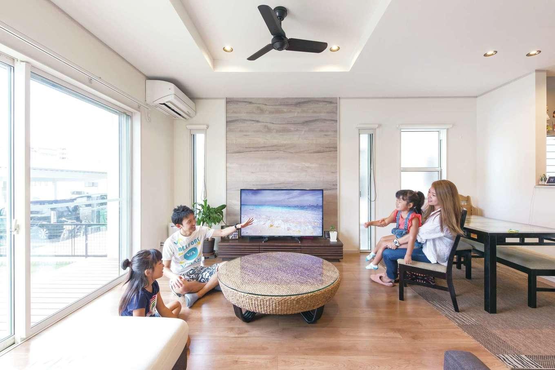 東海ハウス【デザイン住宅、1000万円台、間取り】大きな窓から広さと明るさがもたらされ、実際の面積以上のゆとりが溶け込む。テレビ背後には木目のフローリングを採用。空間にメリハリが生まれ、目線も落ち着く
