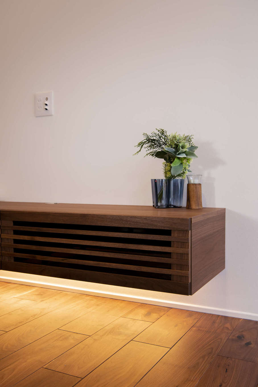 無垢の床材と色見を揃えたオーダーメイドのTVボード。TVボード下部に取り付けた間接照明が、高級感を演出