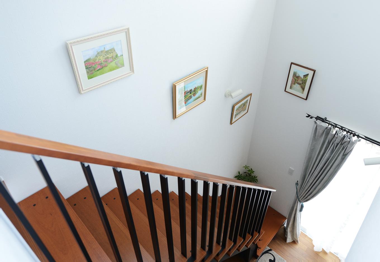 ハウスコネクト【輸入住宅】この階段そのものがLDKのインテリアさながらで、壁には奥さまが描いた水彩画がずらりと並ぶ。過去に旅したヨーロッパの国々の景色がモチーフ