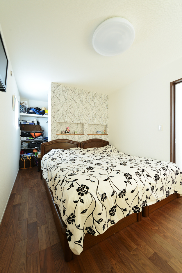 ハウスコネクト【輸入住宅】1階にある夫妻の寝室は大容量のクローゼット付き。収納を隠す壁にはアクセントクロスを選び、空間づくりを楽しんだ