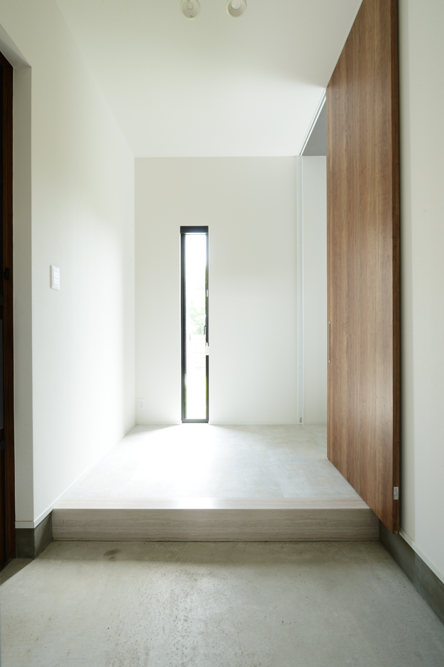 シンプルを極めた意匠が印象的なゲスト用の玄関。家族専用の玄関&シューズクロークは別に設け、そこから裏廊下を通ってLDKにたどり着くようになっている。ゲスト用とは別ルートの動線を設けたことで、玄関を常に美しく整然と保つことができる