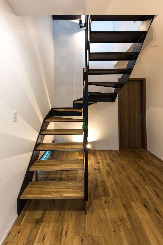 建築システム(狭小住宅専門店)【狭小住宅、間取り、屋上バルコニー】空間を広く見せる開放的なスケルトン階段。アイアンと木調で、LDKと同じヴィンテージ調に統一した。階段下の地窓と照明で足元から明るさを届ける