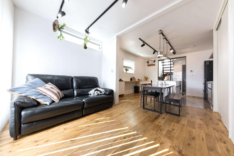 建築システム(狭小住宅専門店)【狭小住宅、間取り、屋上バルコニー】明るい日差しが入る2階リビング。床材にはナラの無垢材を用いて落ち着いた雰囲気に。リビングの照明もスポットライトで個性的に。カフェのようなキッチンは、ステンレスの質感でシャープな印象