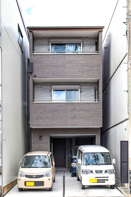 建築システム(狭小住宅専門店)【収納力、狭小住宅、ガレージ】隣り合う家との隙間はわずか。この敷地に3台駐車可能な3階建てを実現。外観はシックで落ち着いた木目調のサイディングでまとめた
