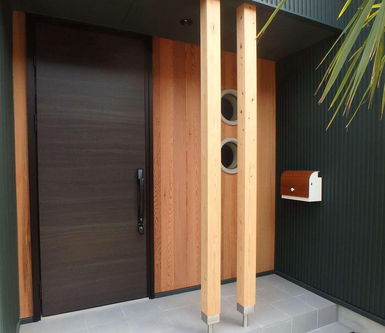 RIKYU (リキュー)【デザイン住宅、趣味、建築家】丸窓のある玄関ドアにもこだわりを感じる。玄関ポーチに貼ったナチュレウォールがアクセントに