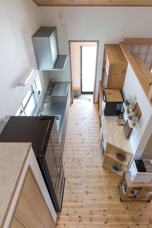 建築システム(狭小住宅専門店)【1000万円台、自然素材、平屋】ロフト部分からキッチンを見おろす。壁で閉じられていないので開放感がある。奥には土間に通じる開口部が。冷蔵庫の手前にはクローゼットタイプのパントリーを設けてある