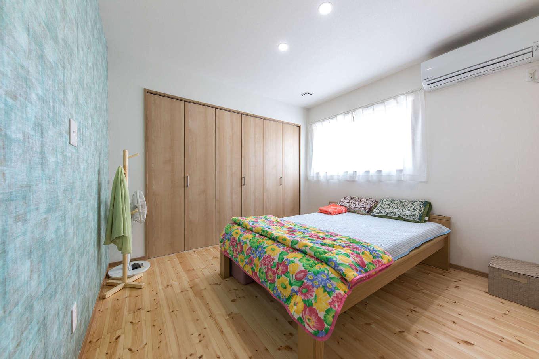 建築システム(狭小住宅専門店)【1000万円台、自然素材、平屋】壁の一面をクローゼットしてシンプルにまとめた寝室。ブルー系のアクセントクロスが爽やか
