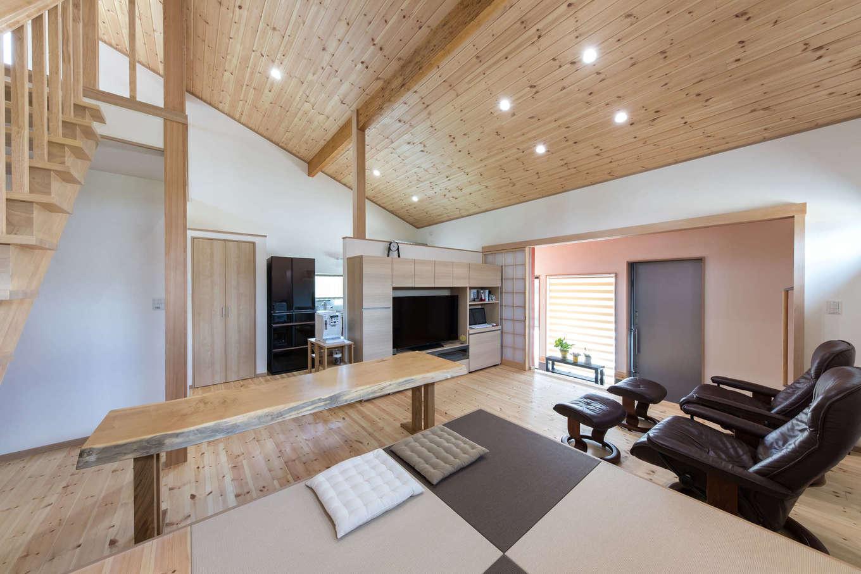 建築システム(狭小住宅専門店)【1000万円台、自然素材、平屋】床と勾配天井にパイン材を用いたLDK。収納棚とパソコンコーナーも兼ねた造作のテレビボードをキッチンとの仕切りに。小上がりの畳コーナーを椅子がわりに使う、一枚板のテーブルも大工の造作で