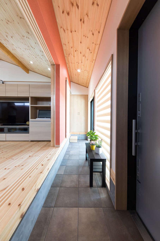建築システム(狭小住宅専門店)【1000万円台、自然素材、平屋】玄関土間からそのままリビングへ上がる。土間はキッチンまで続いているので、買い物帰りの奥さまにも優しい動線。壁は木の風合いに合う明るいえんじ色に。窓の外の軒天井にも同じ色を採用している