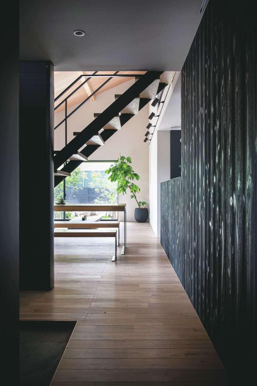 インフィルプラス【浜松市中区上島5-13-17・モデルハウス】玄関の真正面にある黒塗りのスギの壁は、キッチンと寝室の両方向に伸び、空間に連続性を持たせている。仕切りのない一体空間だからこそ、こうしたデザインが成り立つ