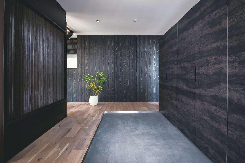 インフィルプラス【浜松市中区上島5-13-17・モデルハウス】モルタルの土間が広がる玄関。無音・無風の「光冷暖」をリビングとの仕切りに利用。反対側の玄関収納の裏は主寝室
