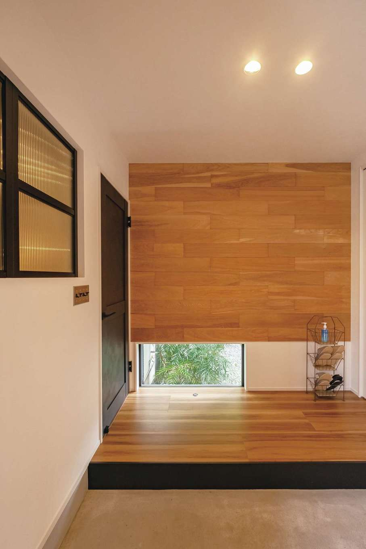 玄関ホールの壁は床材とコーディネートした木材をあしらった。ポイントにもなっている地窓が足元に明かりをもたらし、四季の移ろいを切り取る。リビングとの壁にはご主人の帰宅を気配で感じられるよう室内窓を