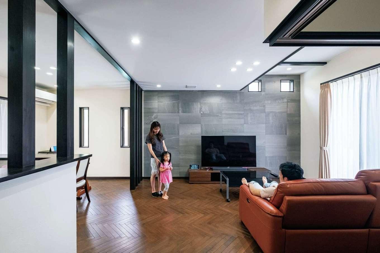 窓側の一部の天井高を3mにした開放的なLDK。フロアには天然無垢材のアカシアを使い、ヘリンボーンに仕上げた。壁には調湿機能のあるエコカラットと珪藻土の塗り壁を採用し、快適な湿度をキープ