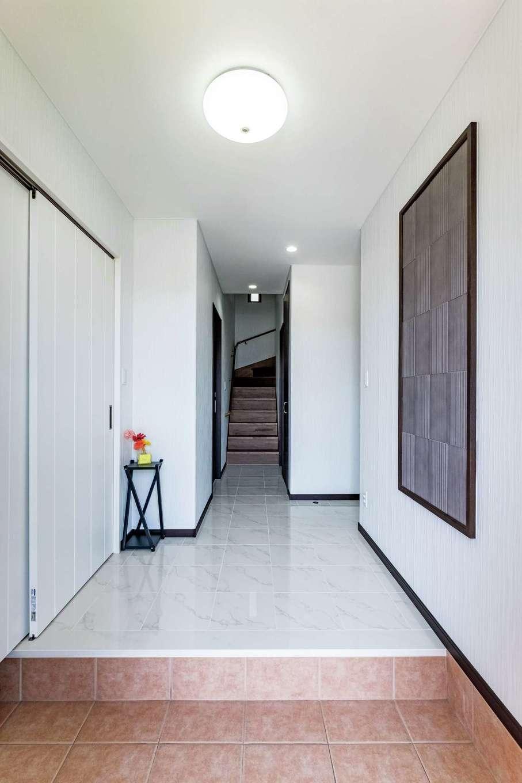 ホールから廊下はゴージャスなタイルを。玄関壁は湿度調整のあるエコカラットを採用し、清々しい爽やかなスペースに。玄関脇には収納力のあるシューズクローゼットを配置