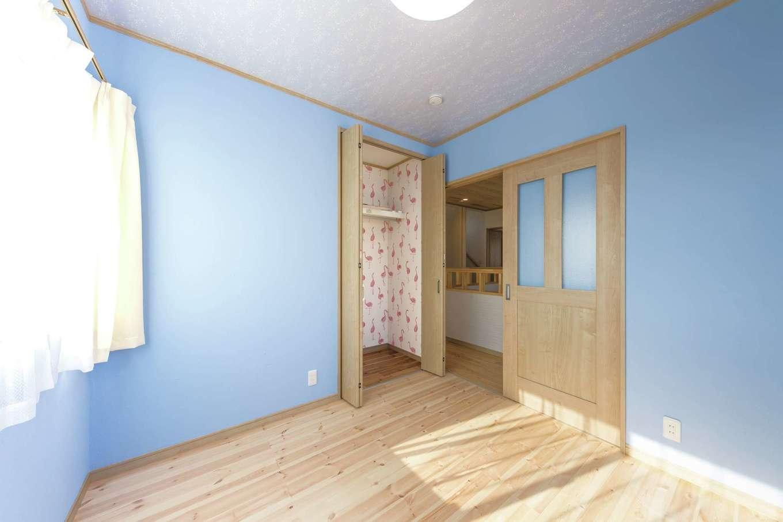 子ども部屋はブルーの塗り壁で爽やかな空間に。クローゼットのフラミンゴ柄のクロスがキュート