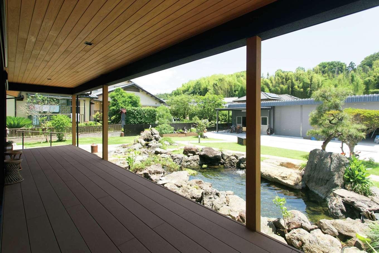 深い軒下のウッドデッキは「ぬれ縁」として機能し、四季折々の庭の景色を楽しめる。池の水音にも癒やされる