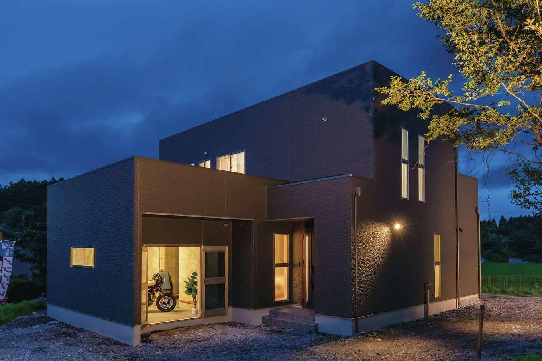 インナーバイクガレージを備えたT邸。高級感のあるブラックの外壁が緑豊かな自然に映える