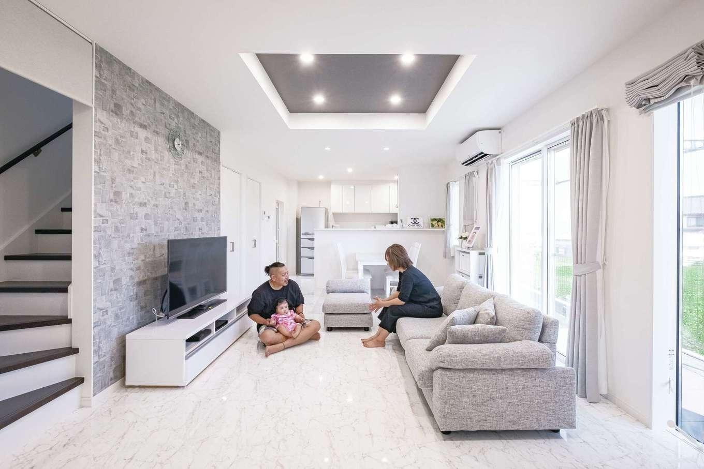 白とグレーで統一したLDK。折り上げ天井を採用し、空間をより広く見せている。リビング階段はロールスクリーンで冷暖房効率をキープ