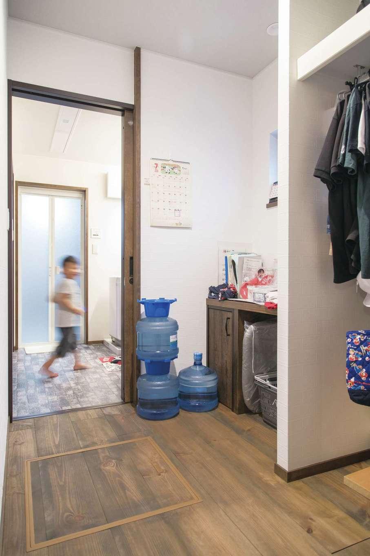 TDホーム静岡西 ウエストンホームズ【デザイン住宅、和風、自然素材】キッチンと脱衣室のあいだに配置された家事室には、造作のテーブルとともにハンガーパイプを用意。幼稚園のカバンや帽子もここに置かれ、LDKのスッキリに貢献