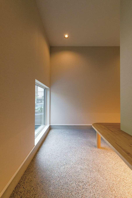 地窓から明かりが入るゆったりとした広さの玄関土間には、L字型にベンチを造作。来客と腰掛けておしゃべりも。夜は間接照明で落ち着きある佇まいに
