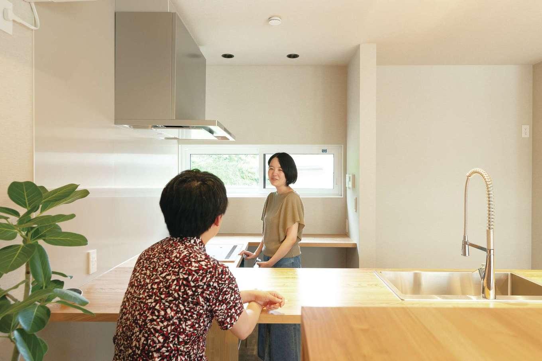 コの字型の広々としたキッチン。天板の広さは作業がしやすいだけでなく、カウンターテーブルがわりにも使える。窓から見える癒しの緑を借景に