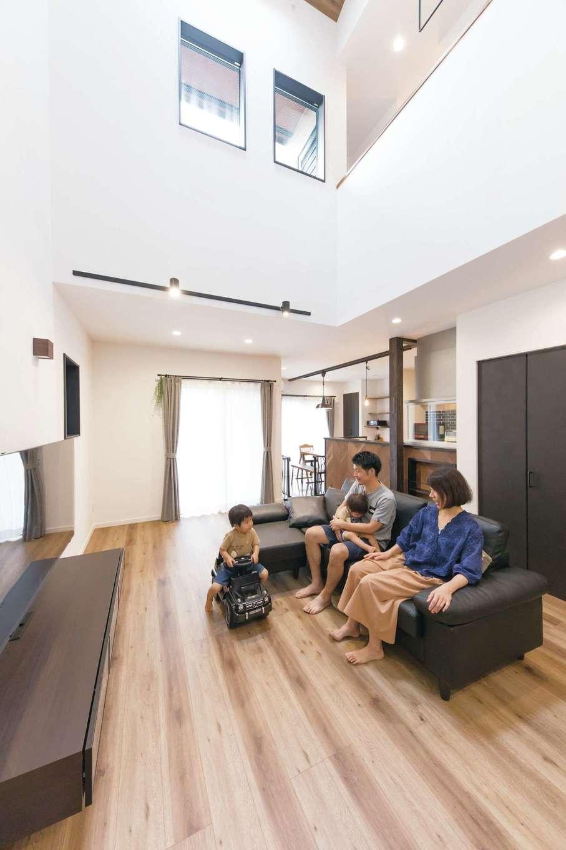 三和建設【デザイン住宅、収納力、間取り】階下に光を届けるとともに、縦方向への空間の広がりを演出する吹き抜けリビング。ファミリークローゼットがあるため、来客時には子どものおもちゃなどをすぐ片付けられてすっきり。テーブルは使う時だけ出し、広々とした空間で子どもたちがのびのび遊んでいる
