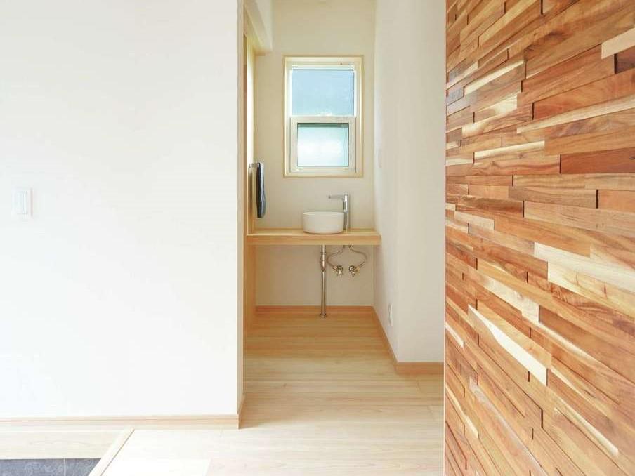 ワイズホーム【自然素材、省エネ、間取り】玄関ホールの壁の一部にはインパクトのある木のデザインウォールを用いた