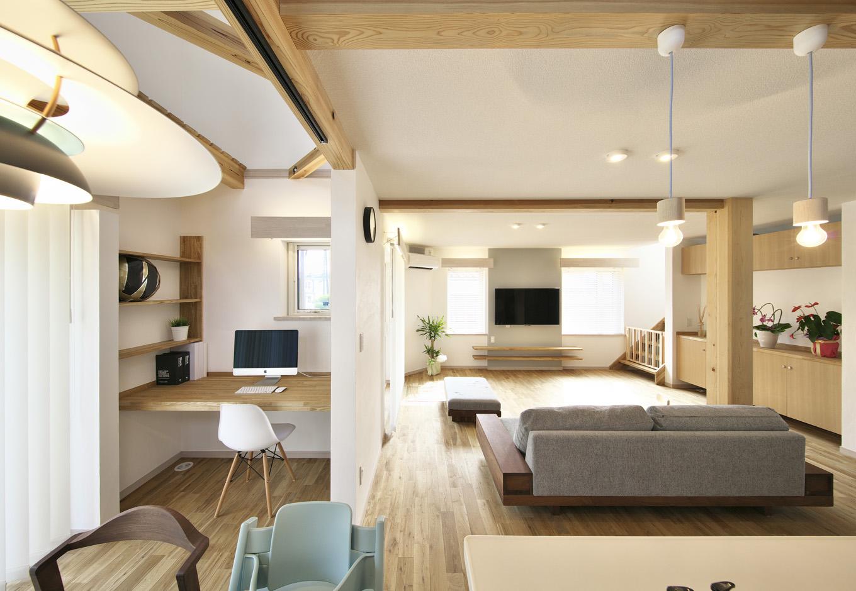吹き抜けから柔らかな光が降り注ぐLDKは建具がなくオープンな空間。オークの無垢の床板にスイス漆喰の白、アクセントにライトグレーのクロスを使うことで、シンプルながらもおしゃれな空間に仕上げた