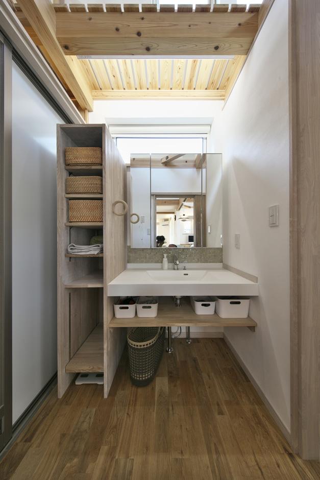 奥様こだわりのオリジナル洗面台には、ガラス製のタイルを使用。高い位置に窓を設けることで、暗くなりがちな洗面所を明るい雰囲気に