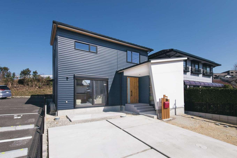 くらはし建築【デザイン住宅、収納力、間取り】ガルバリウム鋼板がモダンな外観は、塗り壁や木製ドアとのバランスがいい。玄関前には外部物置スペースがあり、自転車や冬用タイヤの保管ができる。夏には日陰を利用し、BBQやプールにも最適