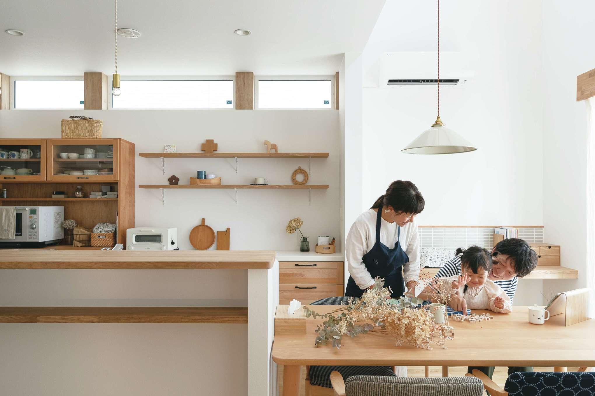 ainoa.life くらはし建築【デザイン住宅、収納力、省エネ】キッチンとダイニングが一直線に並び、回遊できるレイアウトを採用。ダイニングの奥にはタイルをあしらったカウンターを設け、パソコンや家事などに使う。『くらはし建築』は設計前にお宅訪問するのが恒例。どんな暮らしをしているか、何を大切にしているかを知ることで、より本質的な提案をしたいから。事前に採寸した食器棚がピタリと収まり、キッチンバックに並んだ北欧雑貨やマルシェで買った日用品が、日々の暮らしに彩りを与えてくれる