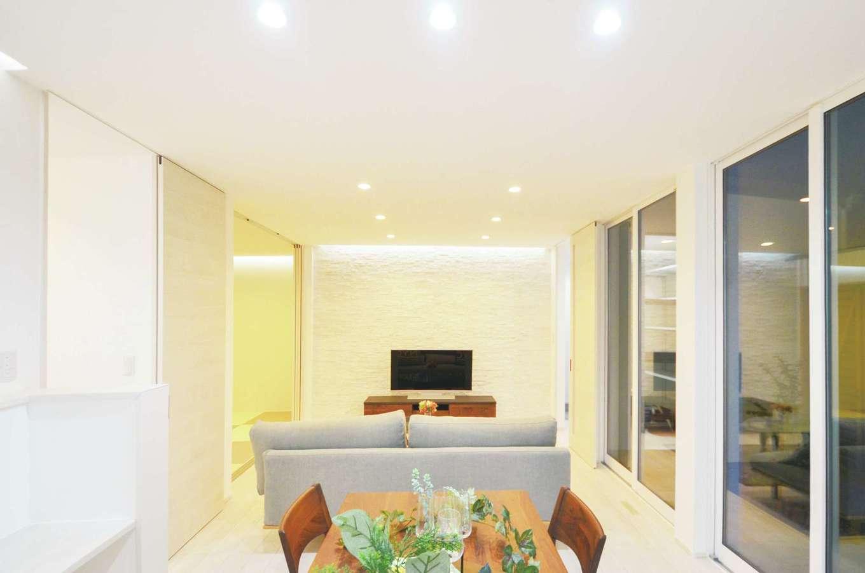 ティアラホームスタイル【デザイン住宅、省エネ、間取り】テレビ後ろのタイルの壁には間接照明を入れ、立体感と高級感を演出。タイルの裏には畜熱体が入っていて、冬の朝も室内は冷え切らずやさしい暖かさを保ってくれる