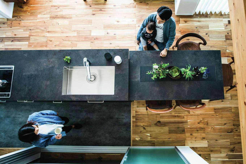 深いグレーのキッチンと、無垢アカシアの床のコントラストが美しい