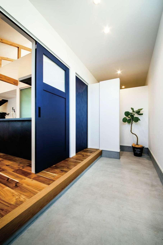 玄関土間の手前からリビングに続くドア、キッチンに面したドアが並ぶ。壁の奥にはシューズクローク兼家族用玄関もある