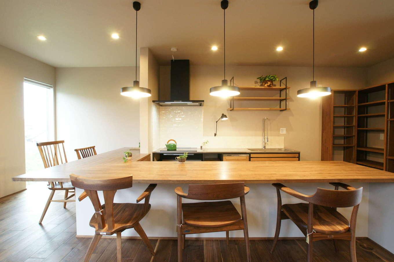 RIKYU (リキュー)【デザイン住宅、建築家、ガレージ】カフェスタイルの対面キッチン。L字型の造作テーブルでキッチンを囲み、レストランのような雰囲気で食卓を囲む。3連のペンダントライトもおしゃれ