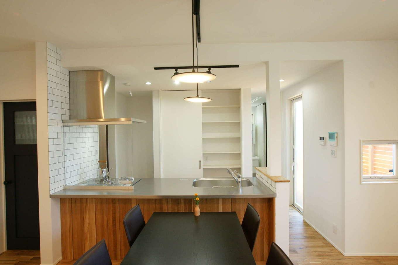 RIKYU (リキュー)【収納力、平屋、インテリア】奥さまこだわりのオープンキッチン。ステンレスのワークトップと木目のパネルがバランス良く調和している。収納も充実