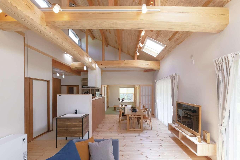 住まいるコーポレーション【デザイン住宅、自然素材、平屋】勾配天井に太い野物の梁がダイナミックに架かったLDKは、広さが約9畳。広い室内に明るさを十分確保するため、勾配天井にトップライトを2か所設置。リビングとダイニングの南面には全開口の掃出窓を設けてあり、常に美しい周囲の風景を見渡せる