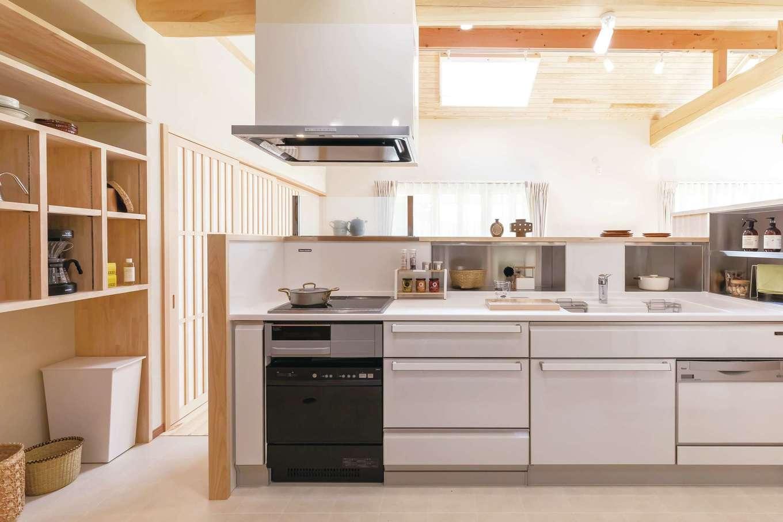 住まいるコーポレーション【デザイン住宅、自然素材、平屋】奥さまの要望で、南向きに設けたアイランドキッチン。腰壁の内側には、鍋や調理器具をしまえるようにステンレス製の棚を造作。マグネットも付けられるようになっているので、キッチン回りがすっきり片付き、調理台スペースを有効に使える。奥さまの使い勝手に合わせて作ったキッチン横の造作棚も便利