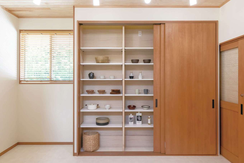 住まいるコーポレーション【デザイン住宅、自然素材、平屋】キッチンの背面の造作収納は、大きな扉で隠してしまえるようになっていて、生活感を隠してLDKをオシャレに演出できる。器や食品などもたっぷりしまえて便利