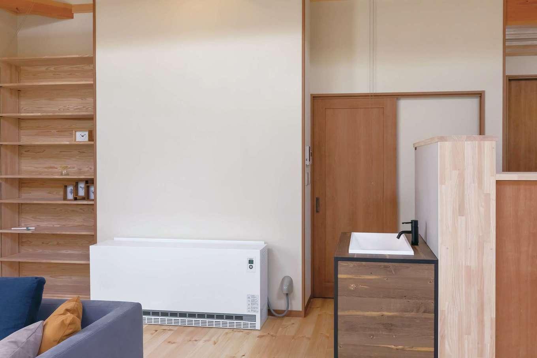 住まいるコーポレーション【デザイン住宅、自然素材、平屋】書棚の隣に蓄熱暖房機を設置。これ1台で冬は家中がぽかぽかと暖まる。夜間の電力を利用するので省エネ性にもすぐれている