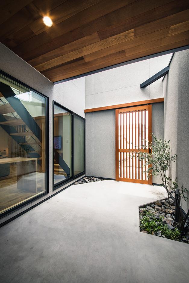 S.CONNECT(エスコネクト)【デザイン住宅、間取り、建築家】玄関ポーチは、防犯性、プライバシーを確保することも考慮し、日当たりのためだけではなく、外観の意匠も夫妻の好みにデザインした。雨水の流れ方や、打合せ当時に起こった集中豪雨などの災害を避ける提案も盛り込まれている