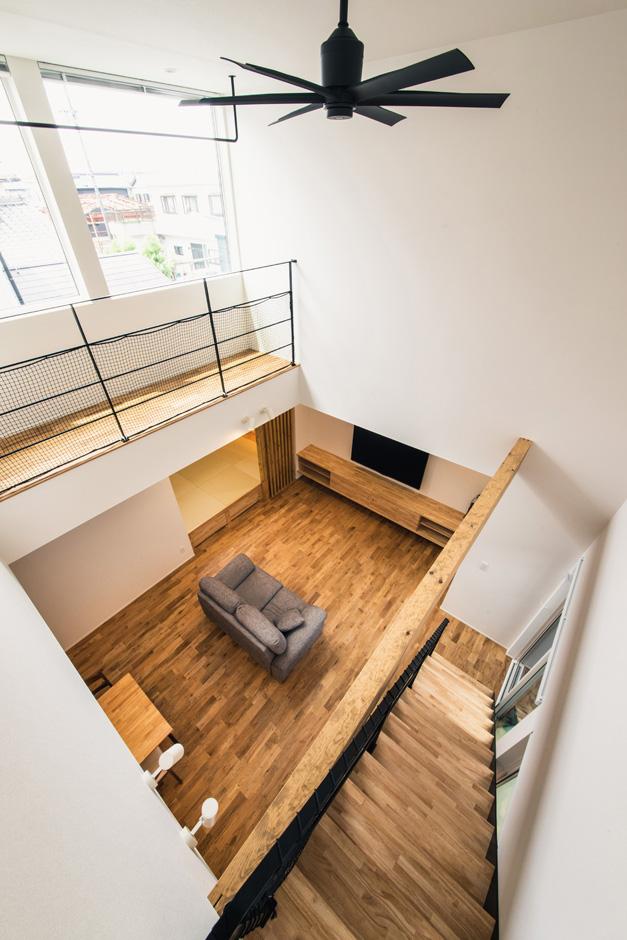 S.CONNECT(エスコネクト)【デザイン住宅、間取り、建築家】2階から吹き抜けのLDKを見下ろす。2階の大窓から光が落ち、無垢フローリングに暖かい陽だまりを創り出す。これだけ広い吹抜けでも、高気密・高断熱の構造により年中快適でエアコンの効率も良い