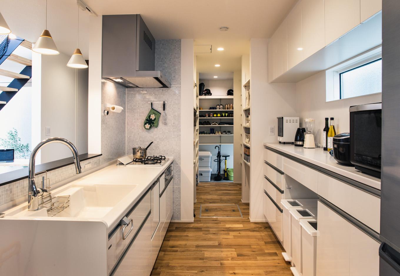 S.CONNECT(エスコネクト)【デザイン住宅、間取り、建築家】対面キッチンの奥にはパントリーがあり、納戸、シューズクロークと一列に繋がっている。買い物帰りに動線上で荷物をしまい込めるのでとても便利!