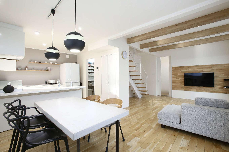 片桐建設【デザイン住宅、収納力、間取り】白・黒・グレーを基調とした21.7畳のLDK。広い空間に繋がりを持たせながら、緩やかにゾーニングされている。リビングとダイニングの天井高を変えたことで空間にメリハリがつく