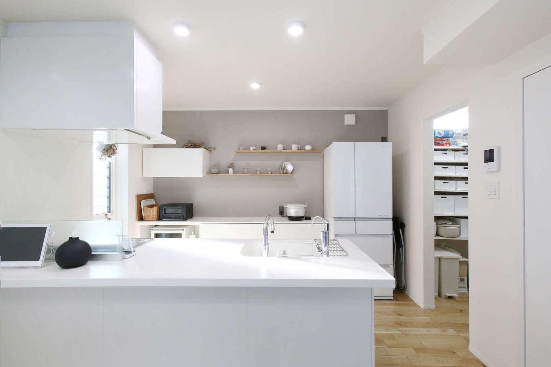片桐建設【デザイン住宅、収納力、間取り】清々しい白で統一したキッチン。生活感が出ないよう、電子レンジを収納スペースに隠した。キッチンからウォークスルータイプのパントリー、洗面所、浴室へと一直線につながる動線が共働き・子育て奥さまの家事時間を短縮する