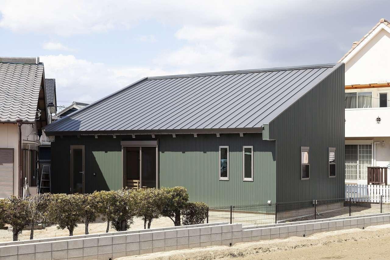 明城【1000万円台、自然素材、平屋】実家の敷地内に建てたK邸。日照と風向きのシミュレーションを実施して建物を配置した。外壁は夫婦の好きなモスグリーンのガルバリウムを採用。大胆な片流れの屋根が印象的