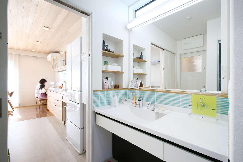 片桐建設【収納力、省エネ、間取り】キッチンからサニタリーへ一直線につながる便利な動線。朝の混雑を想定して、洗面台の鏡は大きめに。奥さまが海外で見つけてきたモザイクタイルが華やぎを与える