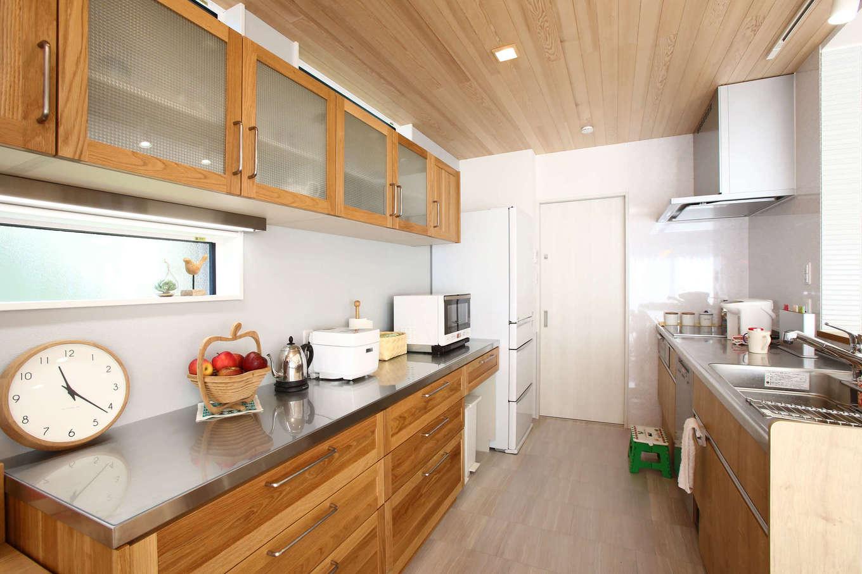 片桐建設【収納力、省エネ、間取り】ご主人も料理を手伝うので、キッチンの作業スペースを広くとった。食器棚も無垢材で造作。3回分の食器を一度に洗浄できる食洗機「ミーレ」が、働く奥さまの家事時間を短縮してくれる