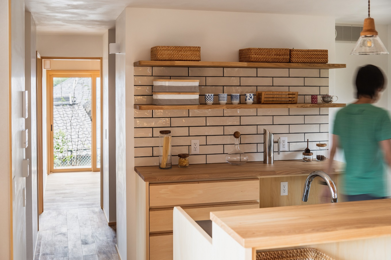 ぴたはうす 安食建設【デザイン住宅、和風、狭小住宅】タイル選びにこだわったキッチン。廊下の奥には水回りとクローゼット、寝室があり、裏庭に通じる