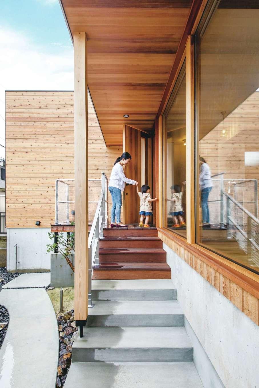 共感住宅 ray-out (レイアウト)【デザイン住宅、子育て、自然素材】奥さまが最も強く望んだ屋根付きのアプローチ。階段の傾斜や幅も身体に負担をかけないよう配慮されている。レッドシダーの軒天と大きな開口部が外観のアクセントに